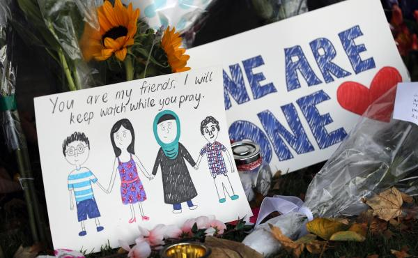 A message card is placed at a collection of flowers left at the Botanical Gardens in Christchurch, New Zealand, on Saturday. A 28-year-old white supremacist stood silently before a judge, accused in mass shootings at two mosques that left dozens of people