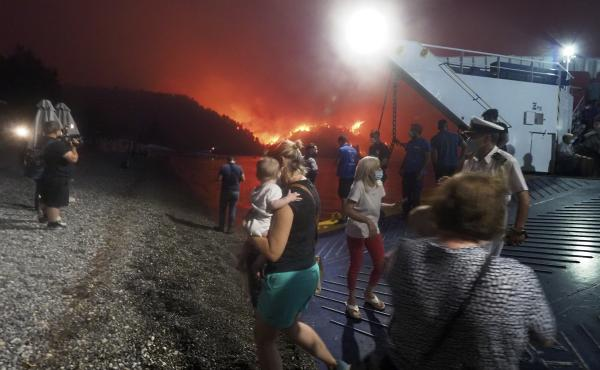 People evacuate from a wildfire north of Athens, Greece, on Friday. A climate-driven heat wave helped create conditions for the fire to burn out of control. Scientists warn that humans are running out of time to curb greenhouse gas emissions and avoid cat