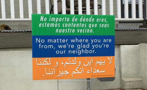 "A sign in Washington, D.C., says ""No matter where you're from, we're glad you're our neighbor,"" in three languages. It's a message that began at a church in Harrisonburg, Va., and is spreading to communities across the country."
