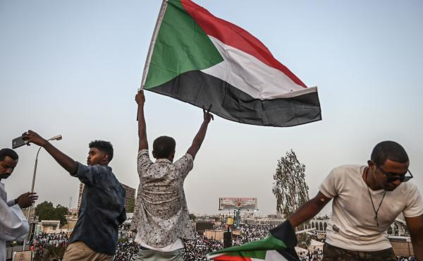 A Sudanese protester waves a national flag on a bridge during a protest outside the army headquarters in the capital Khartoum on April 19, 2019.