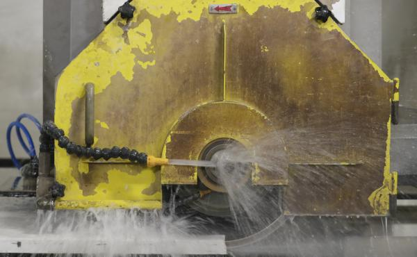 Water applied to cutting equipment, like this computer-operated saw, is one method to control silica dust exposure when cutting quartz slabs.