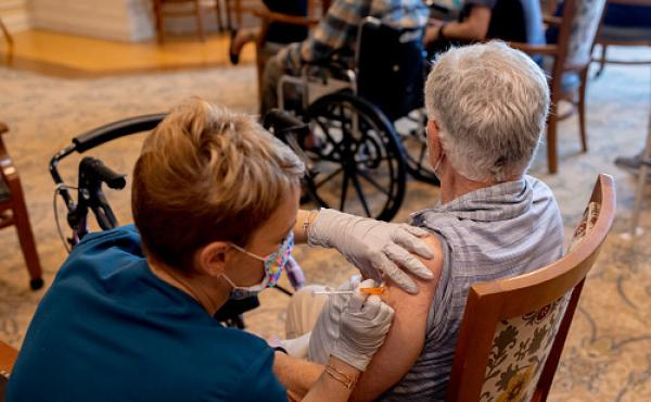 A health care worker administers a third dose of the Pfizer-BioNTech COVID-19 vaccine at a senior living facility in Worcester, Pa., in August.