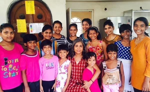 Urmi Basu, center in red dress, with some of the children who live at New Light, the shelter she established.