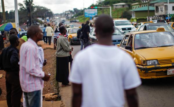 Commuters wait for a ride — usually from a taxi or minivan — at an intersection near Monrovia's Ministry of Health.