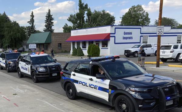 Police cars line up for a procession in honor of an officer who was fatally shot Monday in Arvada, Colo.