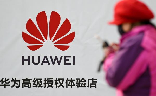 A Justice Department indictment unsealed on Monday details an alleged conspiracy by the Chinese device maker Huawei to steal the details of a T-Mobile robot. Here, a woman uses her smartphone outside a Huawei store in Beijing on Tuesday.