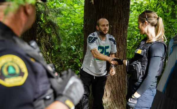 Social worker, Lauren Rainbow (right), meets a man illegally camped in the woods in Snohomish County. They are part of a new program in the county that helps people with addiction, instead of arresting them.