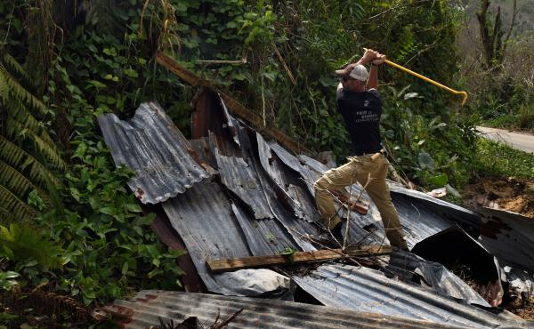 Daniel Braithwaite from Florida, a volunteer who is traveling with troops, gathers materials to repair Ruben Caraballos' leaking roof in Utuado.