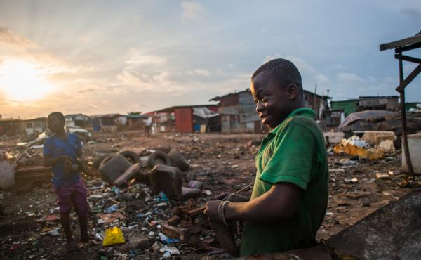 Kwesi Bido, 14, (right) stops to fix 13-year-old Inusa Mohammed's flip flop. Both spend evenings and weekends searching for scrap at Agbogbloshie, an electronic waste dump in Accra, Ghana.