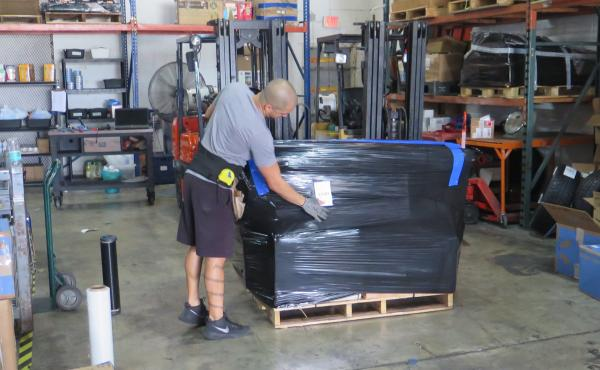 A worker at VKE Cargo in Miami prepares a pallet containing cargo to be shipped to Venezuela. Fewer shipping companies are willing and able to ship to Venezuela.