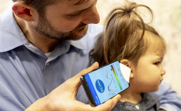 Dr. Randall Bly, an assistant professor of otolaryngology-head and neck surgery at the University of Washington School of Medicine who practices at Seattle Children's Hospital, uses the experimental smartphone app and a paper funnel to check his daughter'