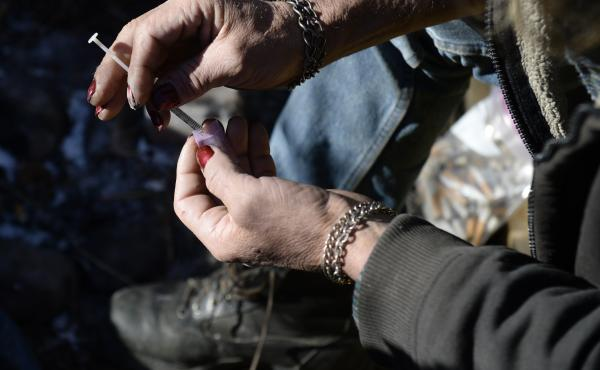 A homeless man in Denver draws heroin into a syringe. Treatment centers in the city say patterns of drug use seem to be changing. While most users once relied on a single drug — typically painkillers or heroin or cocaine — an increas