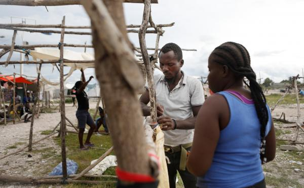 Felina Manita and her husband Jean are building a temporary home out of sticks after losing their home in Les Cayes in the earthquake on Saturday.