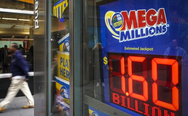 A man walks past a newsstand with advertisements for the Mega Millions lottery on Tuesday in New York City. The $1.537 billion Mega Millions winning lottery ticket was sold in South Carolina.