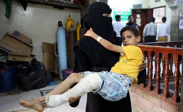 A woman carries a boy to a hospital in Taiz, Yemen. He was injured in an attack by the Houthi rebel group.