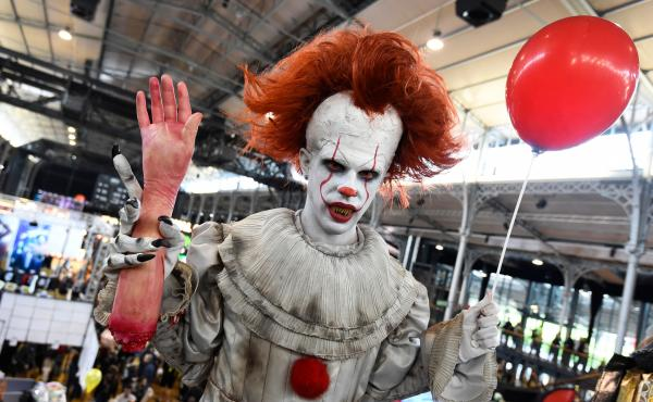 """A cosplayers dressed as Pennywise from """"It"""" poses during the Comic Con festival in 2017 at the Grande Halle de la Villette in Paris."""