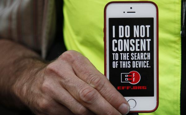 In this 2016 photo, a man holds up his iPhone during a rally in support of data privacy outside the Apple store in San Francisco. Watchdog groups that keep tabs on digital privacy rights are concerned that U.S. Customs and Border Protection agents are sea
