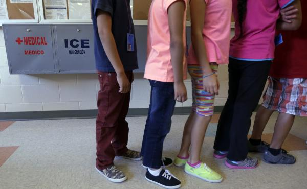 Detained immigrant children line up in the cafeteria at a temporary home for immigrant women and children detained at the border, in Karnes City, Texas.