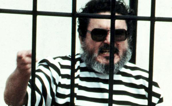 In this Sept. 1992 file photo, Abimael Guzmán, the founder and leader of the Shining Path guerrilla movement, shouts inside of a jail cell after being captured in Lima, Peru. The Peruvian government reported Saturday that Guzman died after an illness.