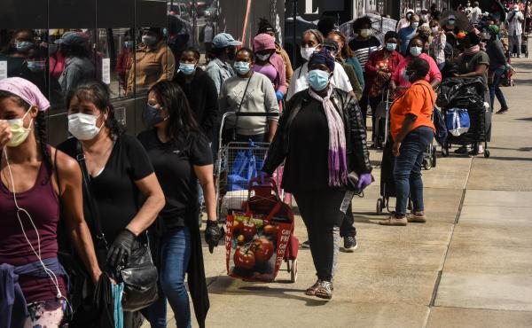 People wait in a long line to receive a food bank donation at the Barclays Center on May 15 in Brooklyn, N.Y. Across the country, cities and towns are dealing with the highest unemployment rates since the Great Depression.