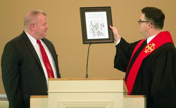 """Nick Wilson (left), at his ordination last month, is given a framed sign from Pastor Matt Johnson that reads """"Just As I Am,"""" the title of one of Wilson's favorite hymns."""