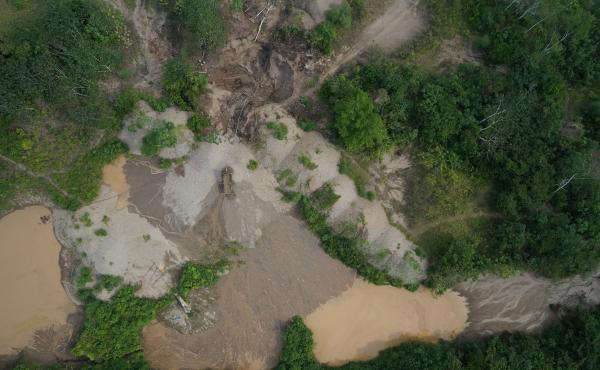 A bird's eye view of a small gold mine in the Madre de Dios region of Peru. The landscape is littered with mines like these, where undisturbed primary forest has been replaced by a gravel and sand landscape laden with mercury.