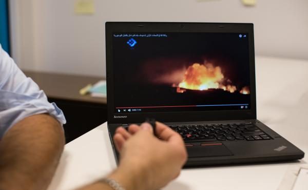 Mohammad Al Abdallah, the executive director of the Syria Justice and Accountability Centre, shows a video that was posted to YouTube of illegal cluster bombing in Syria.