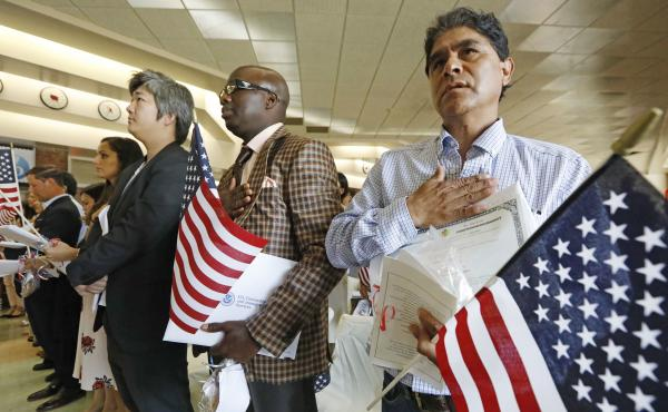 New citizens stand for the U.S. national anthem at a naturalization ceremony in Jackson, Miss., in September 2017. The Census Bureau is considering adding a citizenship question to the 2020 census.