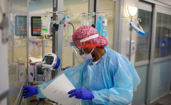 Niticia Mpanga, a registered respiratory therapist, checks on an ICU patient at Oakbend Medical Center in Richmond, Texas. The mortality rates from COVID-19 in ICUs have been decreasing worldwide, doctors say, at least partly because of recent advances in