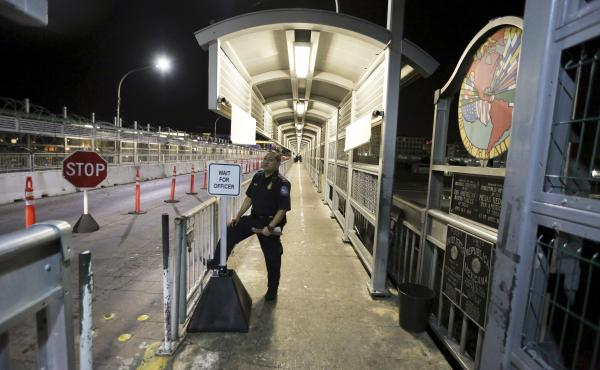 A U.S. Customs and Border Protection officer waits for migrants who are applying for asylum in the U.S. to arrive at International Bridge 1 where they will cross from Nuevo Laredo, Mexico, to Laredo, Texas, early Sept. 17, 2019.