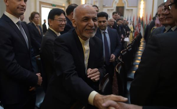 Afghan President Ashraf Ghani shakes hands with a foreign delegate at the Kabul Process conference in the country's capital Wednesday. During the conference, Ghani called on the Taliban to participate in peace talks with the Afghan government.