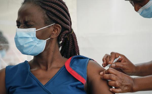 A front-line worker in Kenya receives a shot of the AstraZeneca COVID-19 vaccine. African Family Holistic Health Organization in Portland, Ore., hopes that the work it does in the U.S. will help curb vaccine misinformation back in Africa.