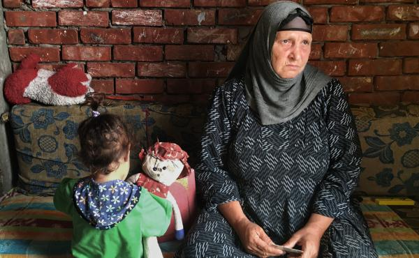 Suad Thabet sits with her granddaughter Sandy at home in Abu Qarqas, Egypt. Thabet was attacked by a mob last year after one of her sons was accused of having an affair with a Muslim woman.