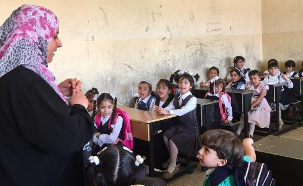 A teacher greets students on the first day of elementary school in Mosul, where regular classes have started for the first time since ISIS took over the northern Iraqi city three years ago. Hundreds of schools were damaged or destroyed in the fighting to