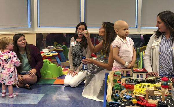 "Melania Trump blows bubbles in a playroom with children during a visit to Monroe Carell Jr. Children's Hospital in Nashville, Tenn., on Tuesday. The first lady was promoting her ""Be Best"" campaign to help children."