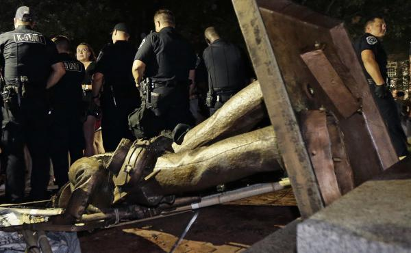 """Police stand guard after the Confederate statue known as """"Silent Sam"""" was toppled by protesters on campus at the University of North Carolina in Chapel Hill, N.C., on Monday."""