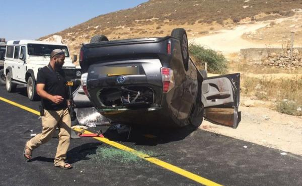 An Israeli security officer next to an overturned vehicle belonging to a family of Jewish settlers ambushed near Hebron, in the West Bank, on July 1. Two Palestinians aided the wounded Israelis. One of the Palestinians has since lost his job and been targ