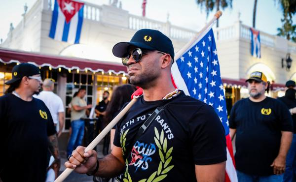 """Henry """"Enrique"""" Tarrio, leader of the Proud Boys, holds a U.S. flag during a July protest in Miami as part of a show of solidarity for Cubans who were demonstrating against their government in Cuba."""