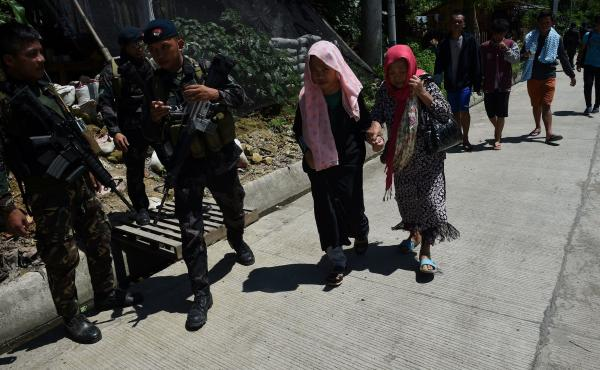 Philippine security forces escort Marawi City evacuees at a checkpoint near a neighboring city on the southern island of Mindanao on Wednesday. President Rodrigo Duterte declared martial law on the island, and government forces have been trying to drive m