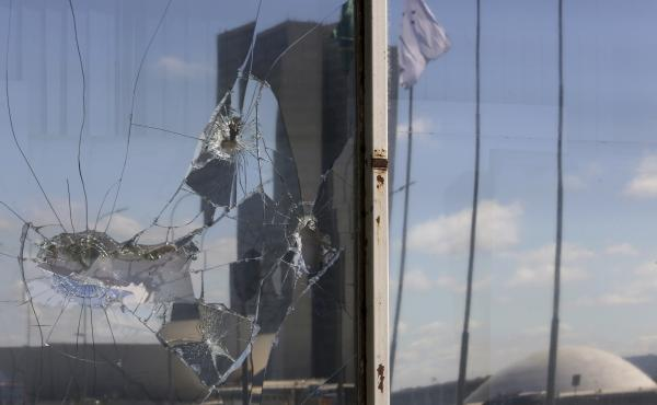The reflection of Brazil's National Congress stands splintered in the broken glass of a federal building in Brasilia on Thursday, one day after protesters flooded the city's streets in opposition to President Michel Temer.