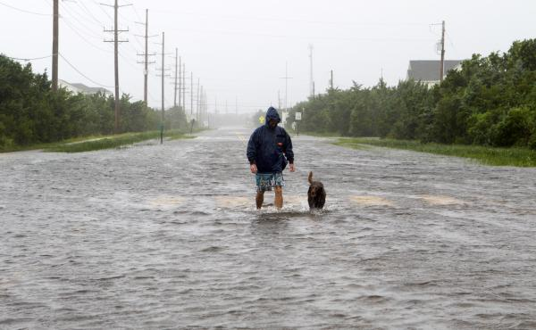 A resident walks his dog on a flooded road Friday in Salvo, N.C., in the Outer Banks, as Hurricane Dorian drenches the neighborhood with a torrential downpour. The storm made landfall Friday morning as a Category 1 hurricane.