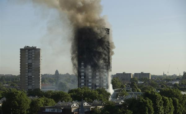 Smoke rises from the Grenfell Tower in west London on Wednesday. A massive fire raced through the 24-story high-rise apartment building overnight.