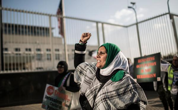 A pro-Palestinian protester raises her fist at a rally outside the U.S. Consulate General in Johannesburg on Tuesday. The South African demonstrators were just some of those who took to city streets to protest the killing of dozens of people along the Gaz
