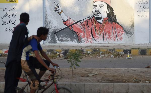 Pakistani cyclists ride past a wall image of late Sufi musician Amjad Sabri alongside a street in Karachi on June 27, 2016.