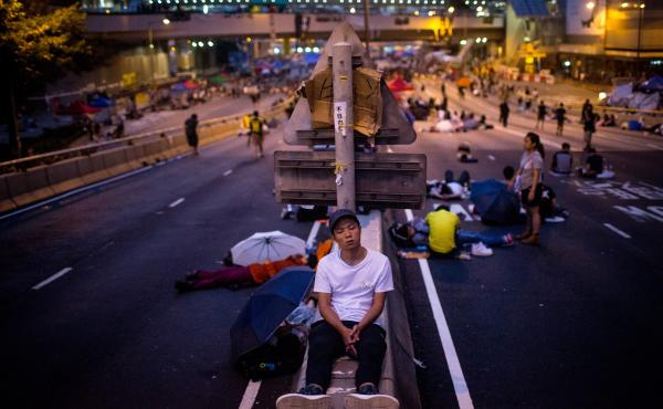 A pro-democracy protester sleeps on a concrete road divider on a street outside the Hong Kong Government Complex on Sunday in Hong Kong.