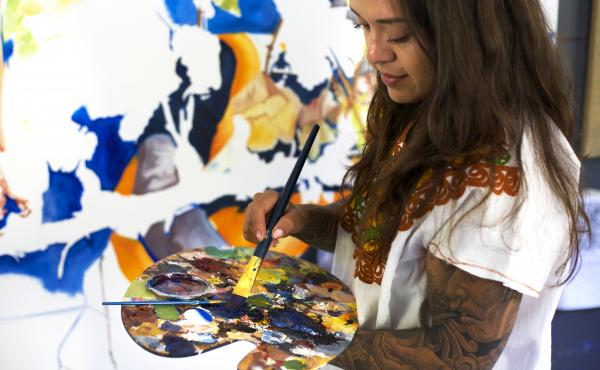 Arleene Correa Valencia works on a painting in her latest series: In Times of Crisis, En Tiempo de Crisis.