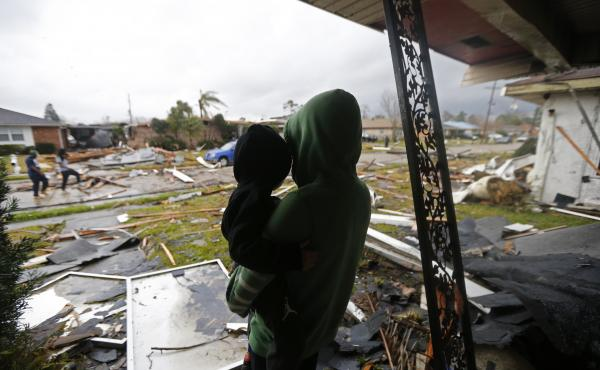 Eshon Trosclair holds her son Camron Chapital on Tuesday after a tornado tore through while they were inside their home in the eastern part of New Orleans. The National Weather Service says at least three confirmed tornadoes touched down, including one in