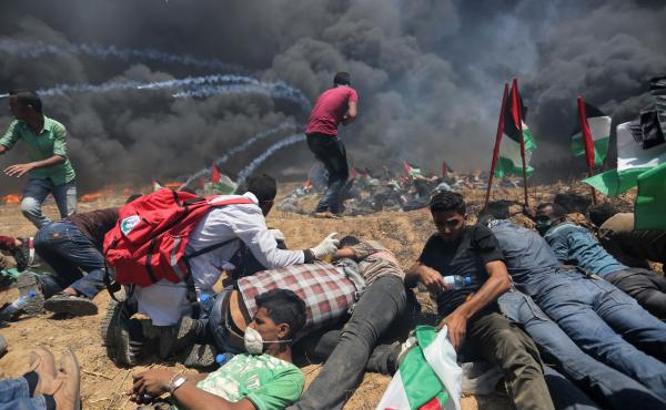 Palestinians set tires on fire, as Israeli soldiers attempt to prevent protesters from breaking through the Gaza-Israel border. The demonstration marked the 70th anniversary of Nakba, or catastrophe, a commemoration of the displacement of hundreds of thou