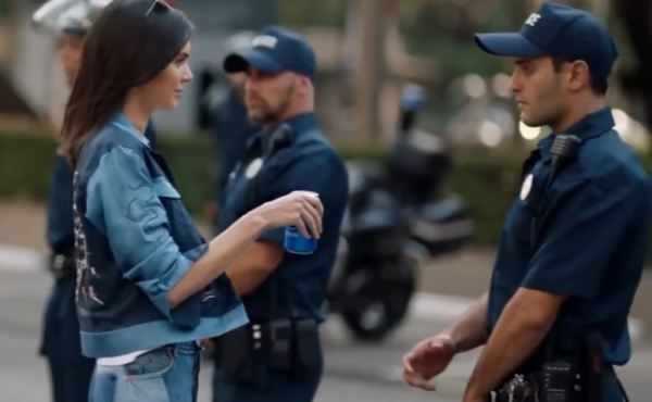 In Pepsi's new ad, model Kendall Jenner joins a protest march and hands a soda to a police officer. Following a widespread backlash, the company announced on Wednesday that it would halt a wider rollout of the video.