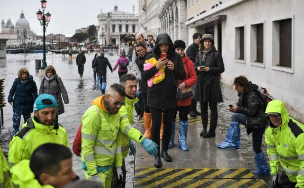 Volunteers set up a footbridge across Venice's flooded Riva degli Schiavoni embankment on Nov. 13.